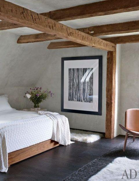 a farmhouse meets vintage bedroom with many wooden beams, a dark stained floor and white plaster walls