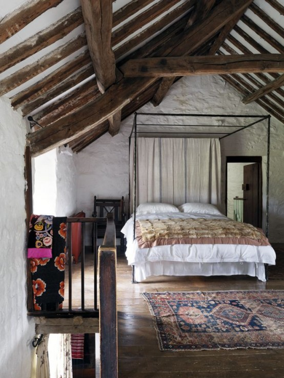 an attic farmhouse bedroom with stone walls and wooden beams, a large metal bed and boho rugs