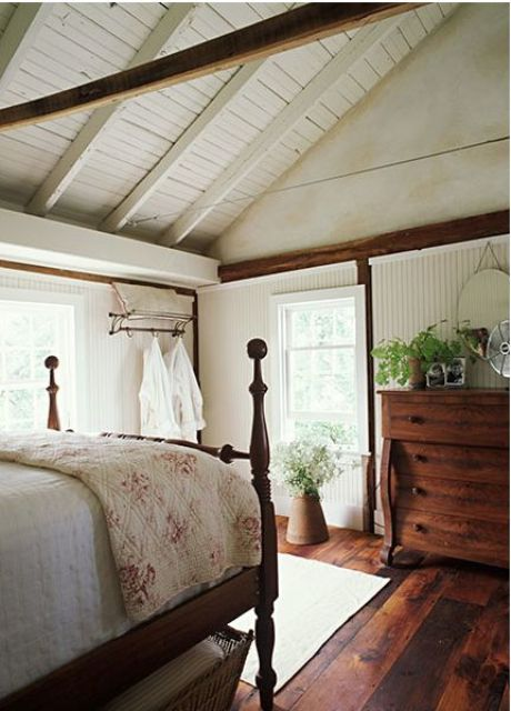 a cozy farmhouse bedroom with a white wooden ceiling plus beams, stained wooden furniture and some printed textiles