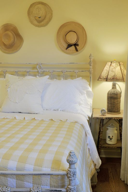 a farmhouse bedroom done in pastels - pastel yellow and blue plus prints and straw hats for decor
