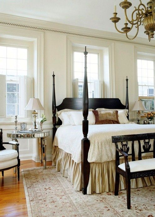 a vintage farmhouse bedroom in neutrals and with dark stained furniture, mirror nightstands and luxurious textiles