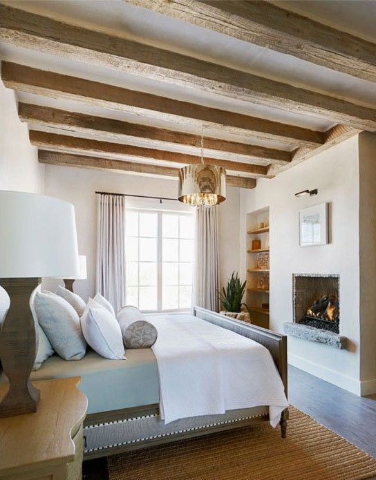 a neutral and chic farmhouse bedroom with wooden beams on the ceiling, a built-in fireplace and elegant furniture
