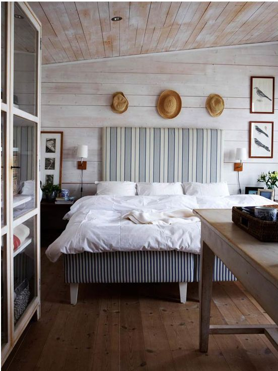 a farmhouse bedroom with whitewashed wood, a striped upholstered bed and straw hats for decor