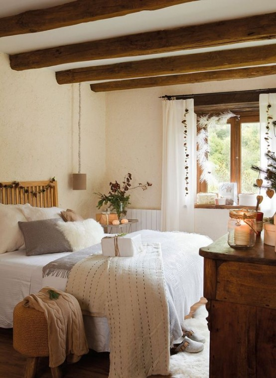 a farmhouse bedroom with wooden beams on the ceiling, hanging lamps and neutral textiles