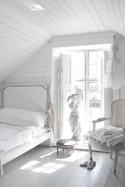 an all-white farmhouse meets vintage bedroom with white wood everywhere, vintage furniture and a sculpture