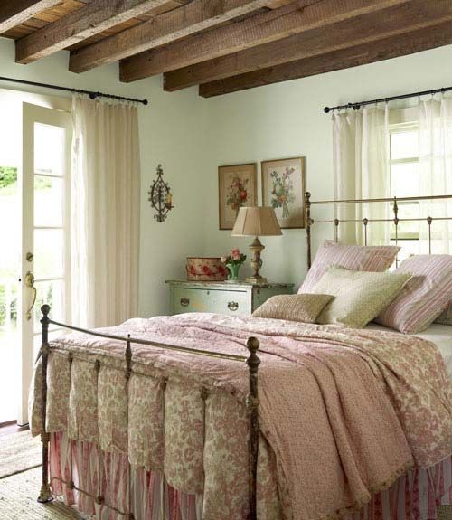 a vintage meets farmhouse bedroom with mint walls, wooden beams on the ceiling and floral print bedding