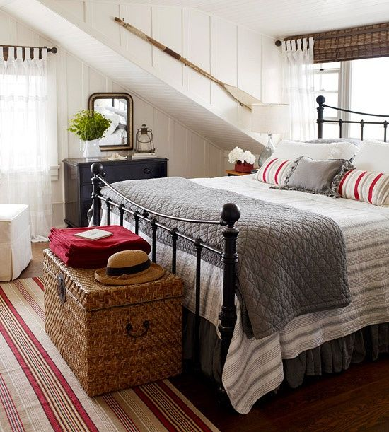 a farmhouse meets beach bedroom with white wooden panels, a wicker chest, a forged bed and beachy touches