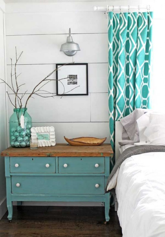 a vintage farmhouse bedroom with white plank walls, vintage furniture and turquoise accents