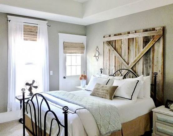 a welcoming farmhouse bedroom with wooden shades and a weathered wood headboard plus a metal bed