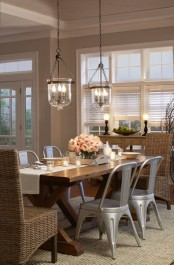 a farmhouse meets glam dining space with a wooden table, metal and wicker chairs, catchy chandeliers and a wooden sideboard