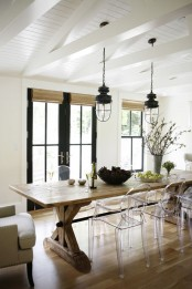 a modern farmhouse dining room with a wooden table, wicker shades, ghost chairs, vintage lanterns and black doors