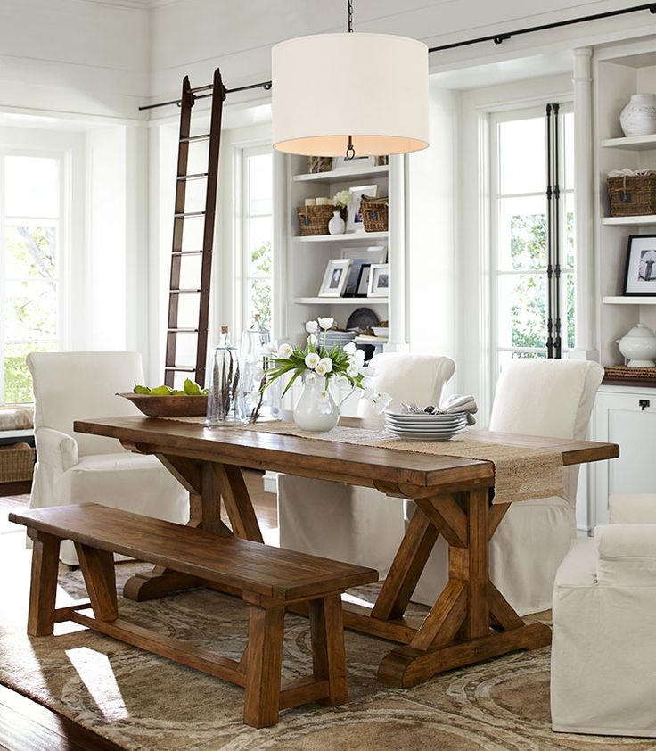 a neutral modern farmhouse dining room with a wooden dining set, some white chairs and built in storage units