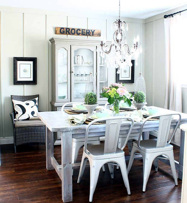 a neutral farmhouse dining area with whitewashed furniture, metal and wicker chairs, a sign and artworks