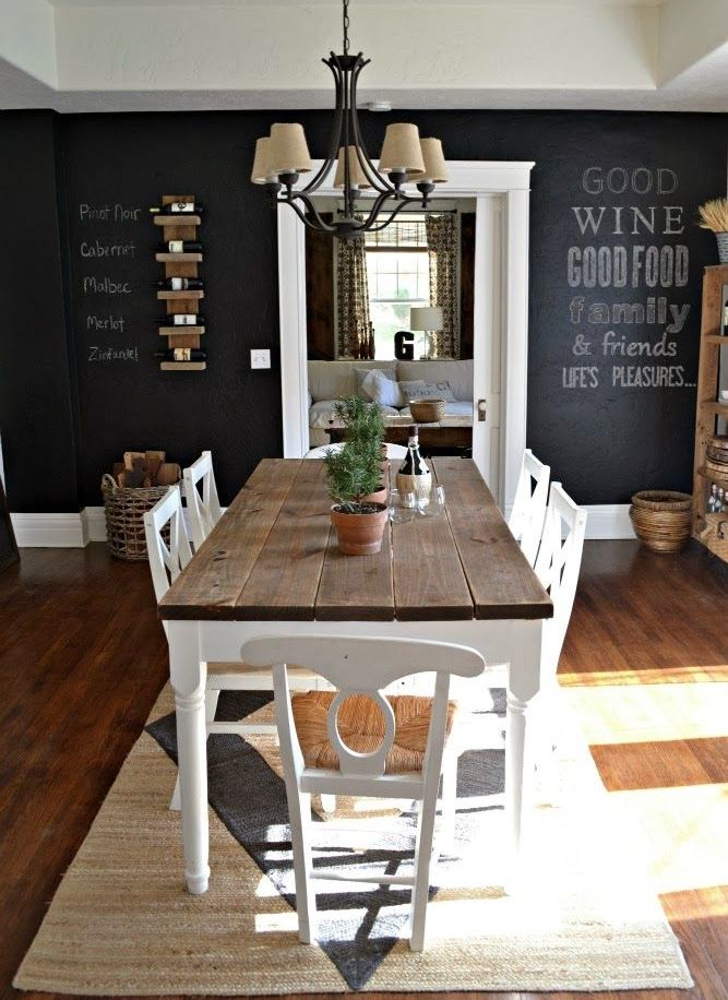 a chic farmhouse dining space with a rustic wooden dining set, a chalkboard wall and a vintage chandelier
