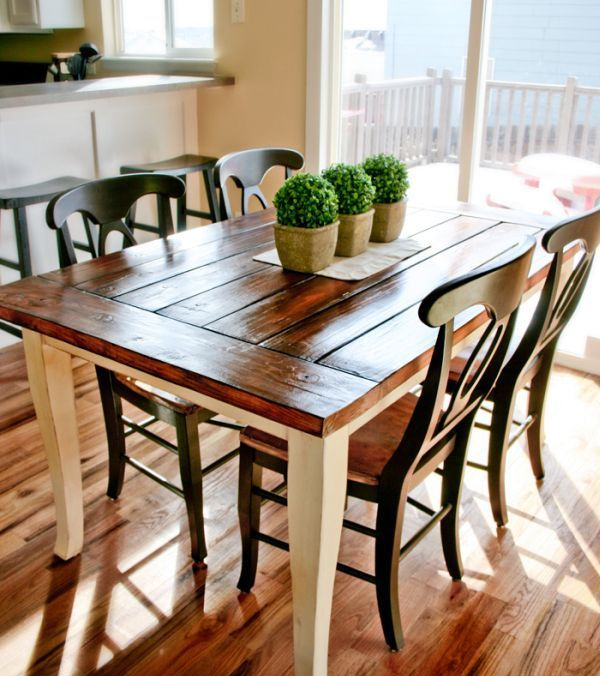a small and simple dining space with a wood clad dining table, wooden chairs and boxwood planters