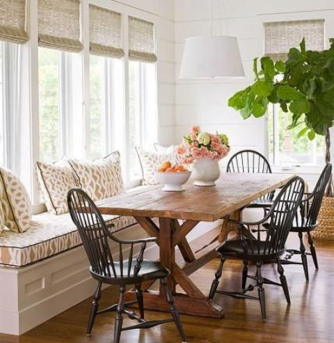 a modern farmhouse dining nook with a windowsill upholstered bench, a wooden table and dark chairs plus wicker shades