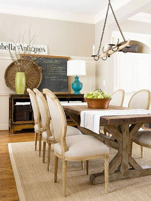 a neutral and welcoming farmhouse dining room with a wooden table, upholstered chairs, a jute rug, a storage unit with baskets and a chalkboard