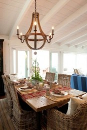 a farmhouse dining space with a wooden table and wicker chairs, a wooden chandelier and greenery