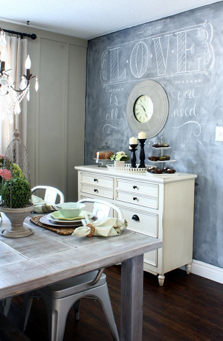 a neutral farmhouse dining room with a chalkboard wall, a white sideboard, whitewashed furniture and a crystal chandelier