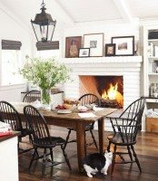 a bright white farmhouse dining space with a white brick fireplace, a wooden table and black chairs, artworks and lanterns
