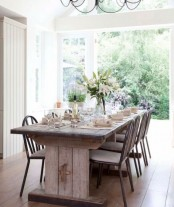 a vintage farmhouse dining area with a vintage dining table and wooden chairs and a view to the garden