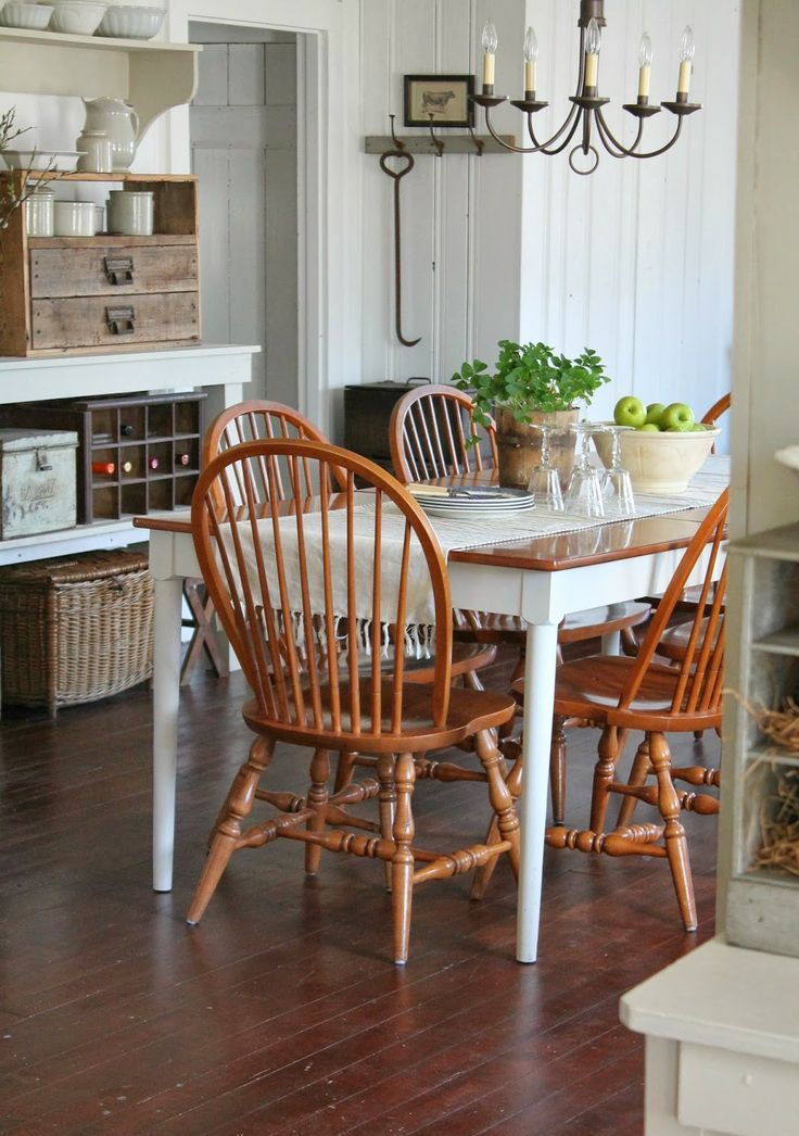 a cozy farmhouse dining space with a wooden table, orange chairs, a large vintage buffet, a vintage chandelier