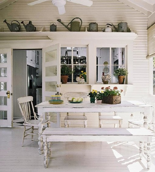 a white farmhouse dining space with shabby chic furniture, watering cans for decor, potted greenery and blooms