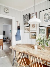 a modern farmhouse dining room with  a chic wooden dining set, a gallery wall and simple white lamps