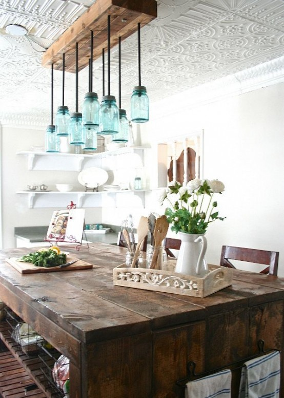 a chic vintage farmhouse dining space with a unique blue jar chandelier, a vintage wooden table and greenery and blooms
