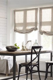 a neutral farmhouse dining space with burlap shades, wood and metal tables and chairs and striped furniture covers