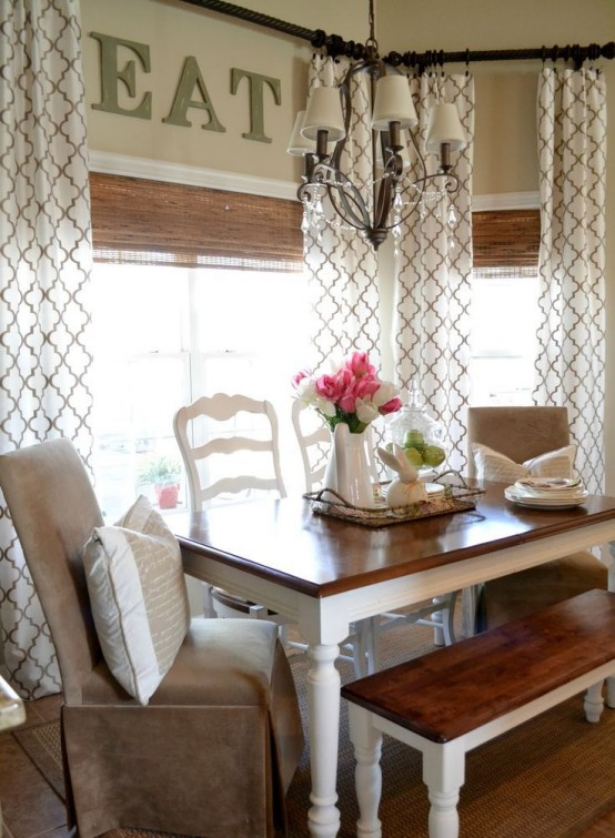 a traditional farmhouse dining room with printed curtains, wicker shades, rustic furniture and leather chairs