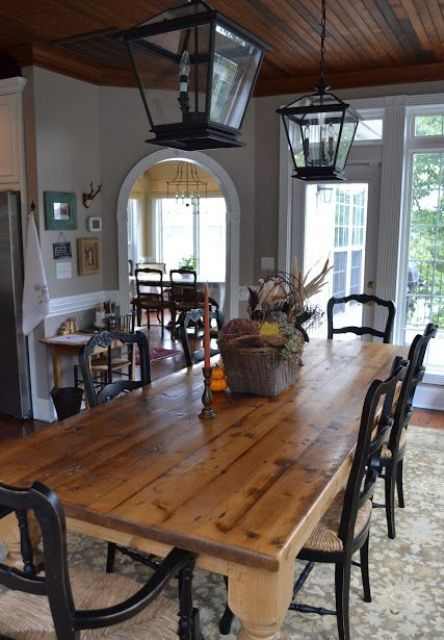 a cozy vintage farmhouse dining room with a wooden table, black painted chars, lanterns and a basket centerpiece