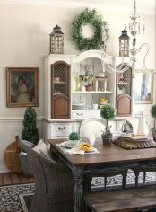 a classic farmhouse dining space with a shabby chic dining set, wicker chairs, a white and brown buffet and beautiful artworks