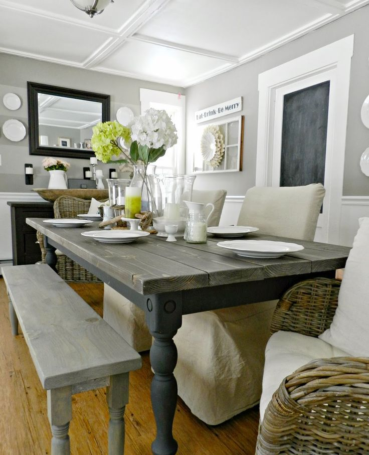 a farmhouse dining space with vintage wooden benches and a table, fabric covered chairs, wicker chairs and a black sideboard