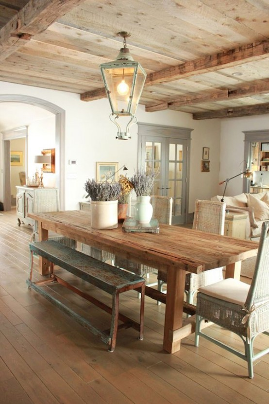 a French farmhouse dining space with a wooden table, patina chairs and benches plus a lantern over the table