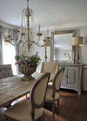a neutral French farmhouse dining room with a vintage dining set, upholstered chairs, a whitewashed sideboard, vintage lamps and a crystal chandelier