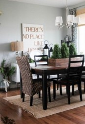 a modern farmhouse dining room with a dark-colored dining set, a wicker chair, a sign and some greenery arrangements