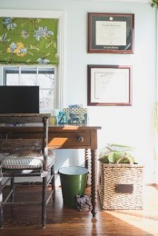 a cozy farmhouse home office with vintage wooden furniture, a bucket for trash and a basket for storage, a green floral curtain and some artworks on the wall