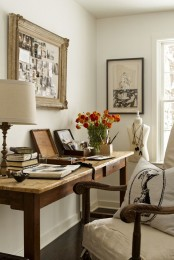 a vintage farmhouse home office with a wooden desk, a refined chair, chic artworks and a table lamp and blooms
