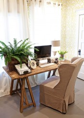 a farmhouse home office with yellow printed wallpaper, a wooden desk and a burlap upholstered chair, potted greenery