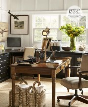 a contrasting farmhouse home office with white walls, black cabinets and desks going along all the walls, a vintage wooden desk,a neutral leather chair and baskets for storage under the desk