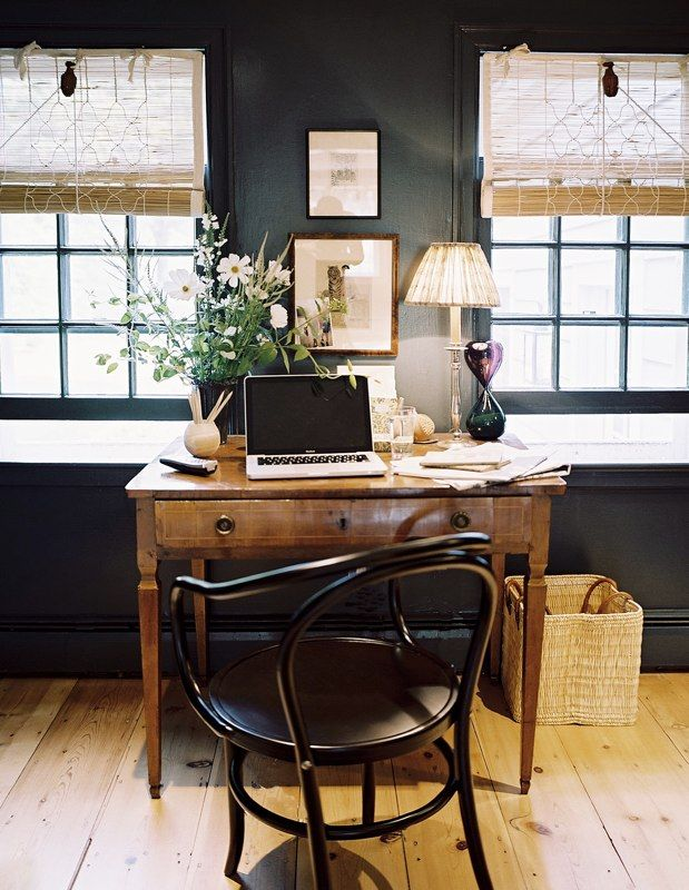 a vintage farmhouse home office with black walls, a wooden desk and a black chair, woven shades and a basket for trash
