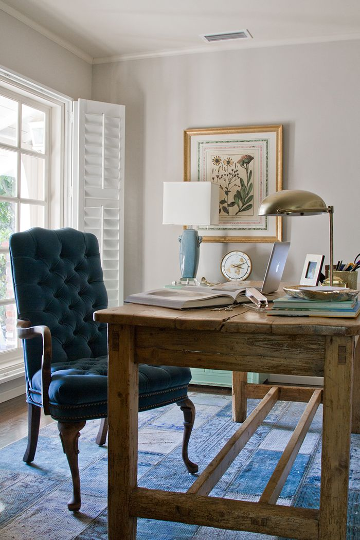 a vintage farmhouse home office with white walls, a vintage wooden desk, a tal velvet chair, a vintage poster and a metal lamp on the desk