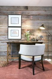 a farmhouse home office with a reclaimed wooden wall, a wooden desk, a white chair, pretty artworks and a red pritned rug is a chic space