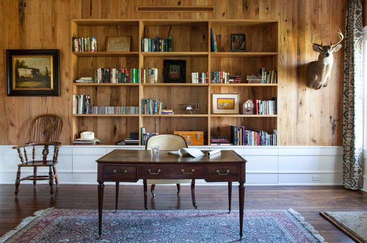 a farmhouse home office with a wood clad wall, built in bookshelves in a niche, a vintage desk and some chairs plus a bold rug