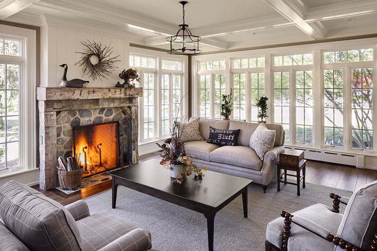 a neutral farmhouse sunroom with a stone clad fireplace, elegant furniture, black vintage tables and a vintage chandelier