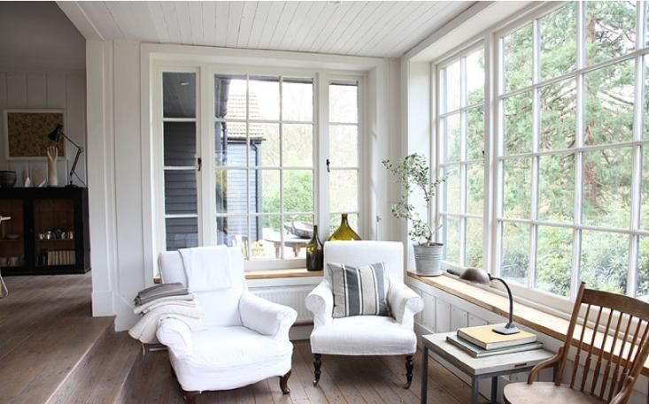 a white farmhouse sunroom nook with vintage furniture, stacks of books and potted greenery is very welcoming