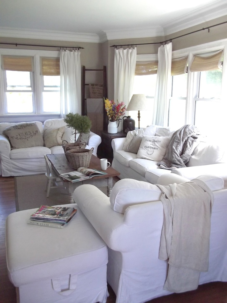 a white vintage farmhouse sunroom with neutral textiles, shades, potted greenery and lamps is welcoming