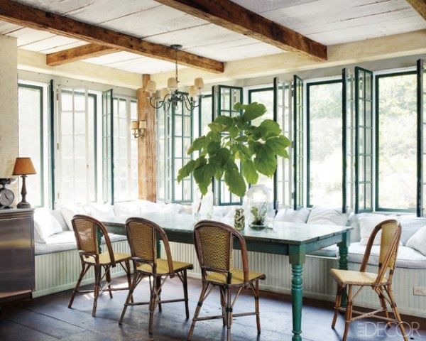 a farmhouse sunroom with a dining zone  with a long L shaped window seat, a blue table and rattan chair plus wooden beams
