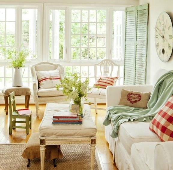 a neutral cozy farmhouse sunroom with white vintage furniture, green shutters and blankets, touches of plaid and stripes plus greenery